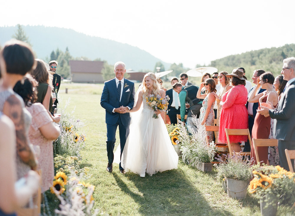 Father of the bride walking down the aisle with bride, sunflower wildflower bouquet and floral design, Sylvie Gil Photography