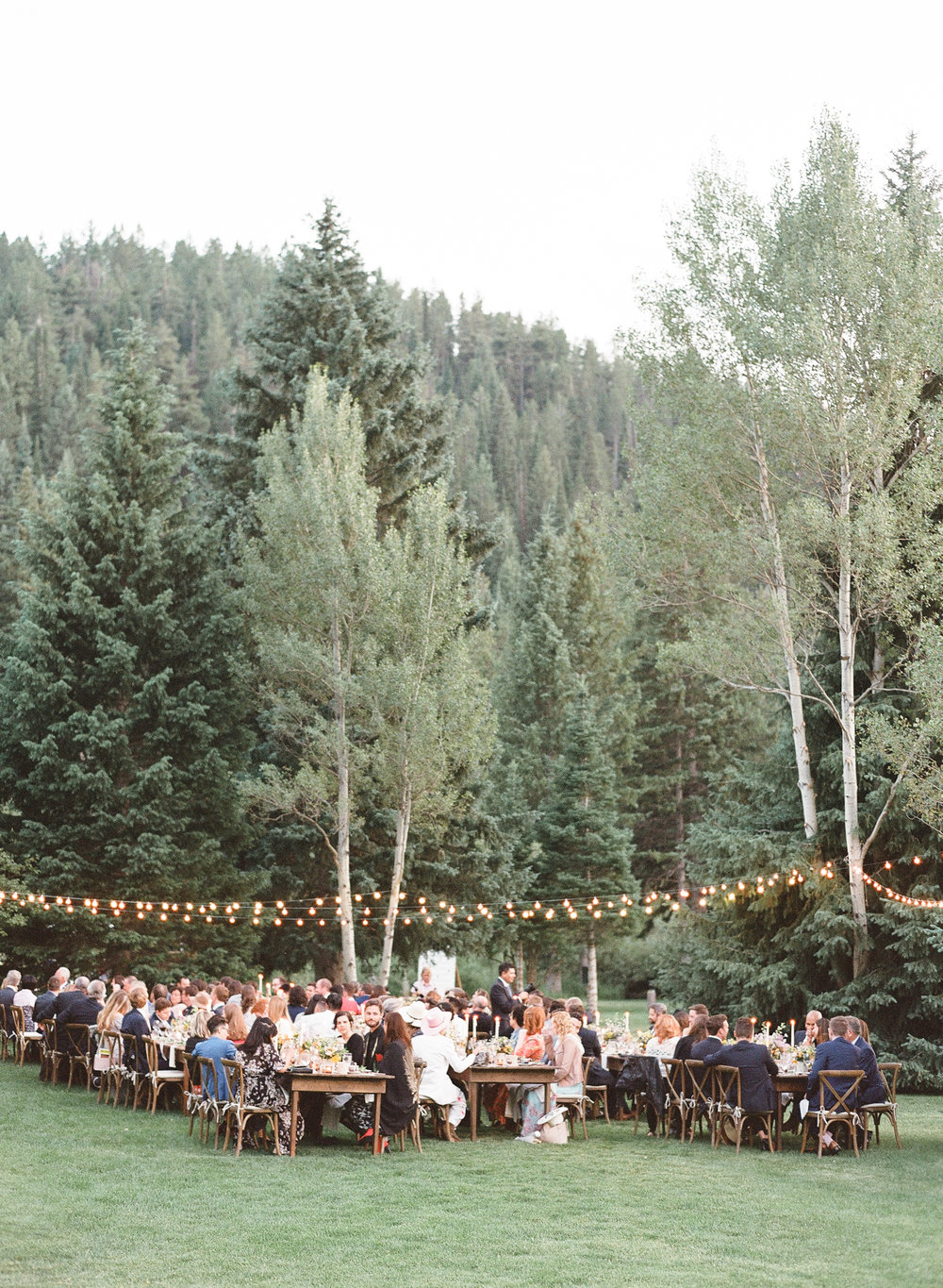 Guests enjoy a beautiful meal under twinkling lights for country wedding, Sylvie Gil Photography