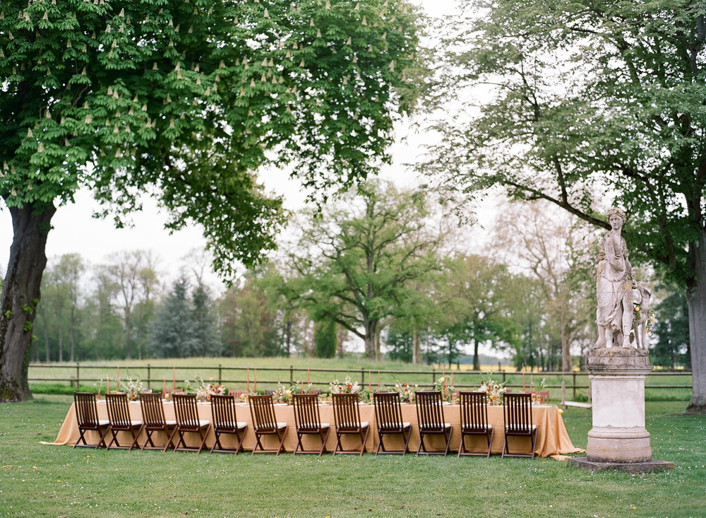 A long reception table in mustard, set up on the grounds of an estate in Burgundy, France; Sylvie Gil Photography