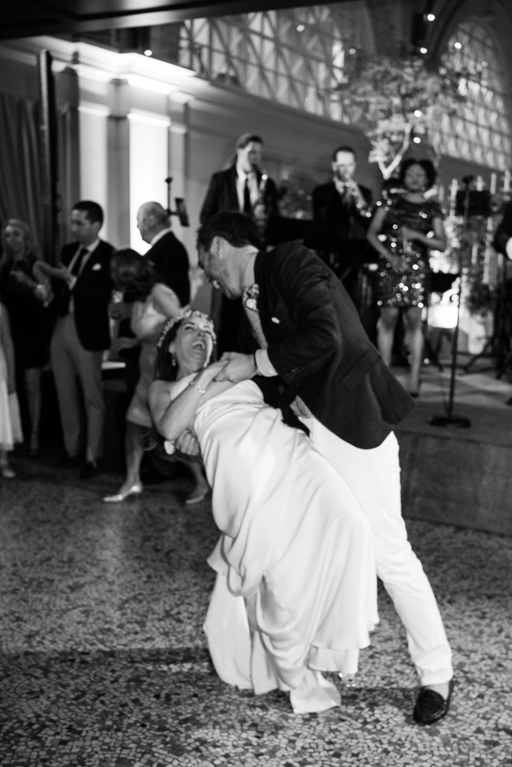 A groom dips his bride at the San Francisco Ferry building; Sylvie Gil Photography