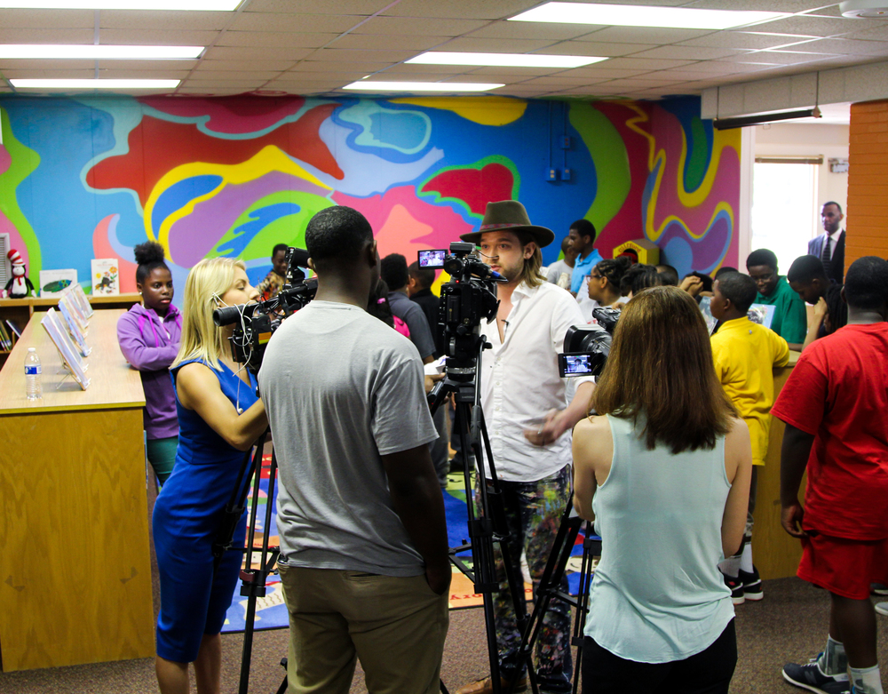 Tripp with Local News Stations in Columbia, SC... interviewing him on the mural he donated to help inspire Sandel Elementary school children.