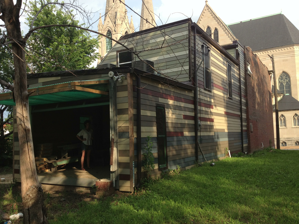 Back and side of the building, including salvaged siding detail. The back opens with a garage door, creating a stage overlooking the back lawn.