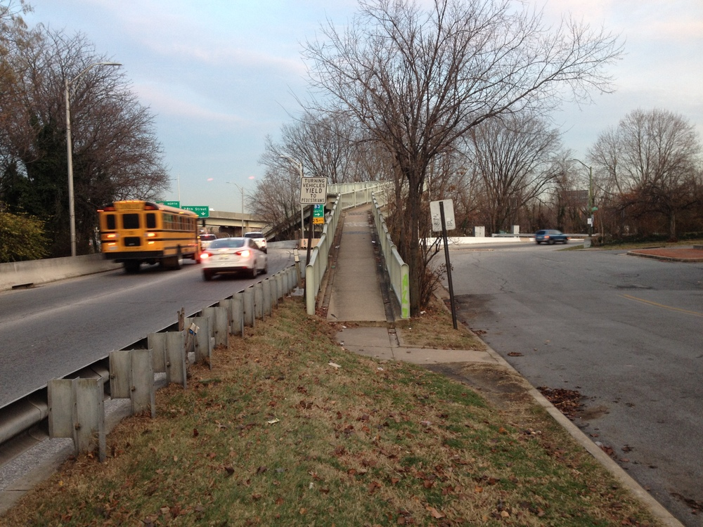 A tear in the space-time fabric of the city: a pedestrian walkway on the west side of Druid Hill park, on-ramp to the east, boulevard to the west, entry via median strip.