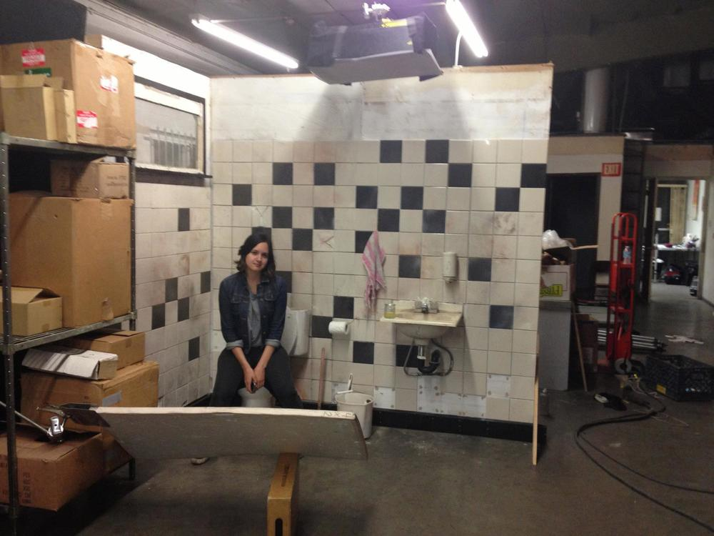 Producer Amanda Garque on the bathroom set.