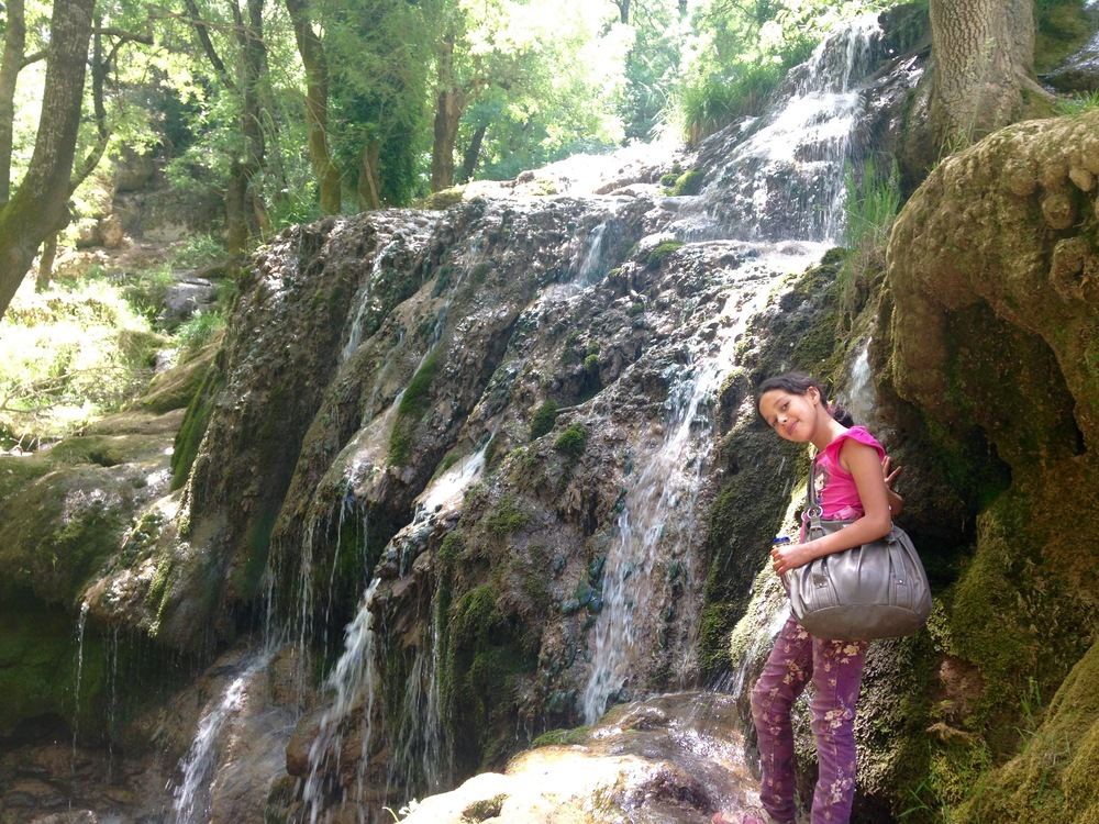 Monia, a student, posing next to our weekly adventure to the waterfall.