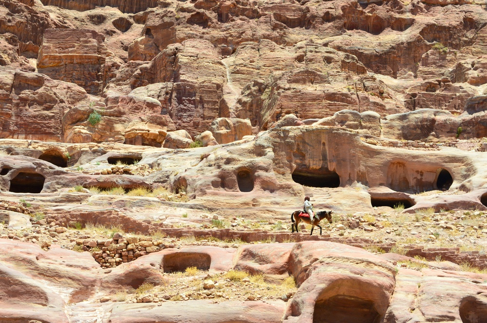 A Bedouin man riding his horse through Petra.