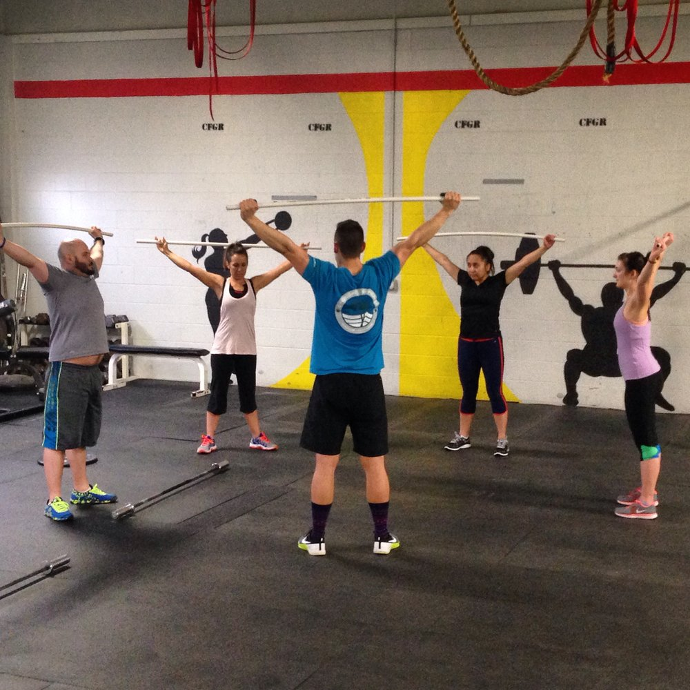 Coach Ryan walking a foundations class through Overhead Squats
