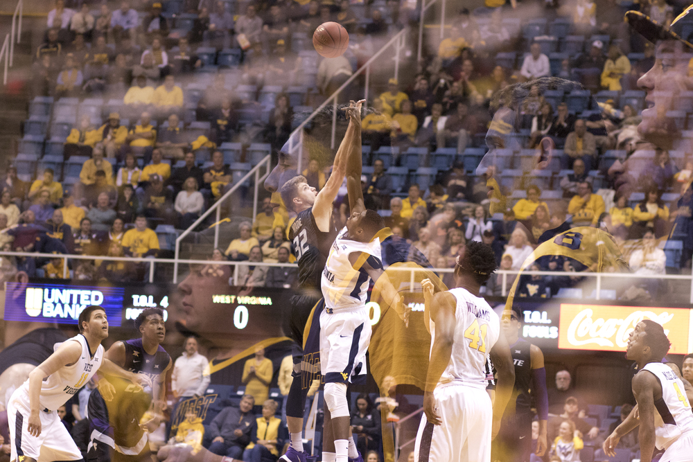 Jonathan Holton goes up for the opening tip as fans watch from the student section.
