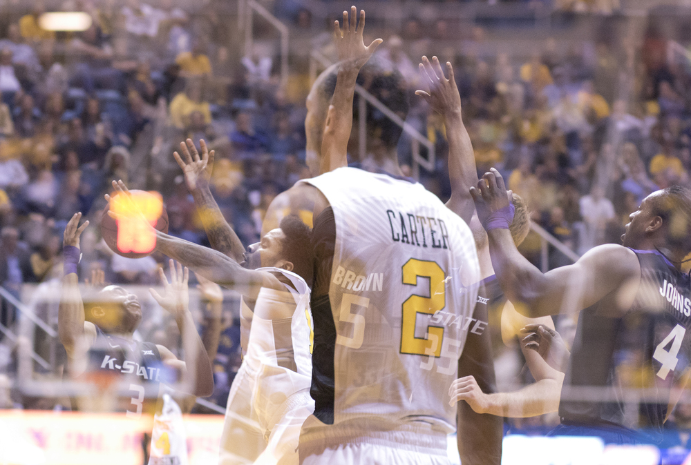 A portrait of Jevon Carter with Tarik Phillip attacking the basket exposed over him.
