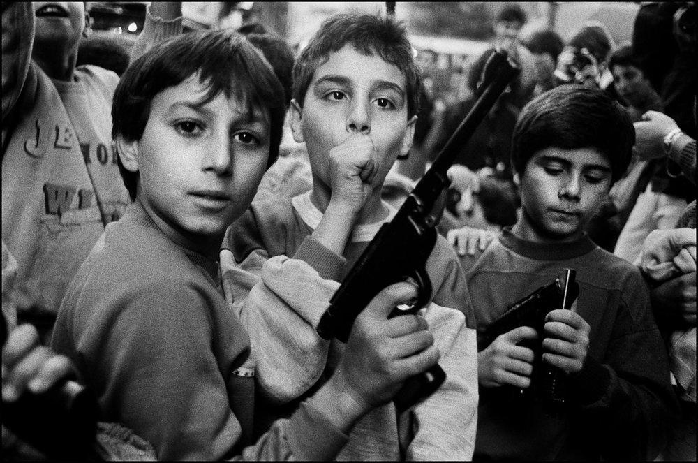 Crianças brincam com as armas que receberam de presente dos pais no 2 de novembro, dia dos mortos, Palermo, 1986. Foto de Letizia Battaglia