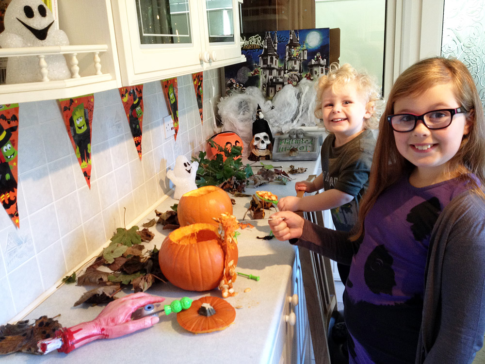 Amber and Jacob having fun carving Halloween pumpkins (well - dad's carving them, they're helping)!
