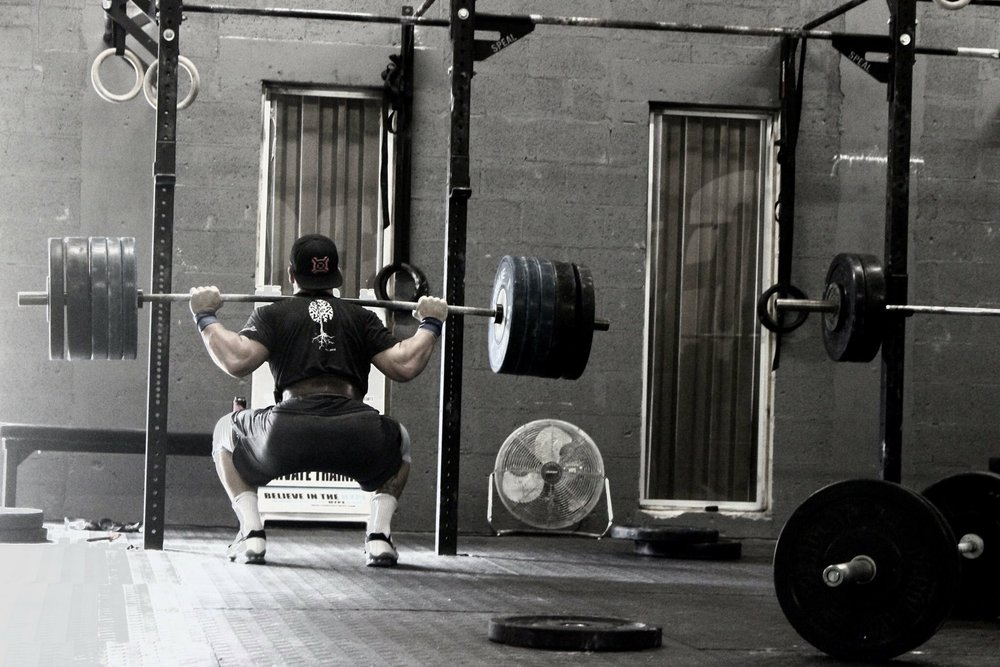 Coach Tim Mustion squatting - CrossFit hype