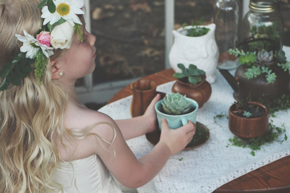 A Succulent Tea Party via Needles + Leaves :: we styled this photo shoot with succulents in a teapot, teacups, mason jars, a bell jar, and terra cotta pots. :: flowers, roses, daisies, babies breath::vintage inspired owl, reused, repurposed, shabby chic, window, candles,miniature furniture:: diy flower crown and little lace dress tutorial.