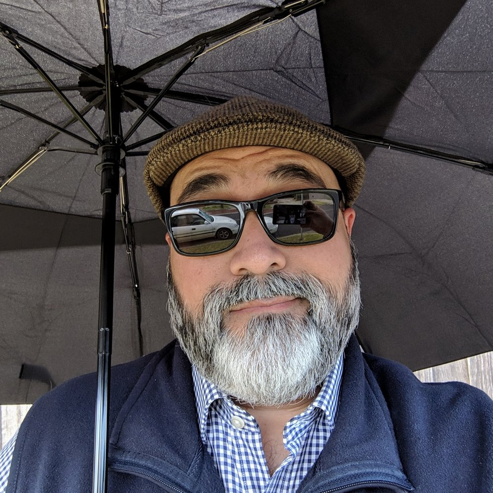 Selfie in sunglasses, sheltering from the rain under an umbrella.