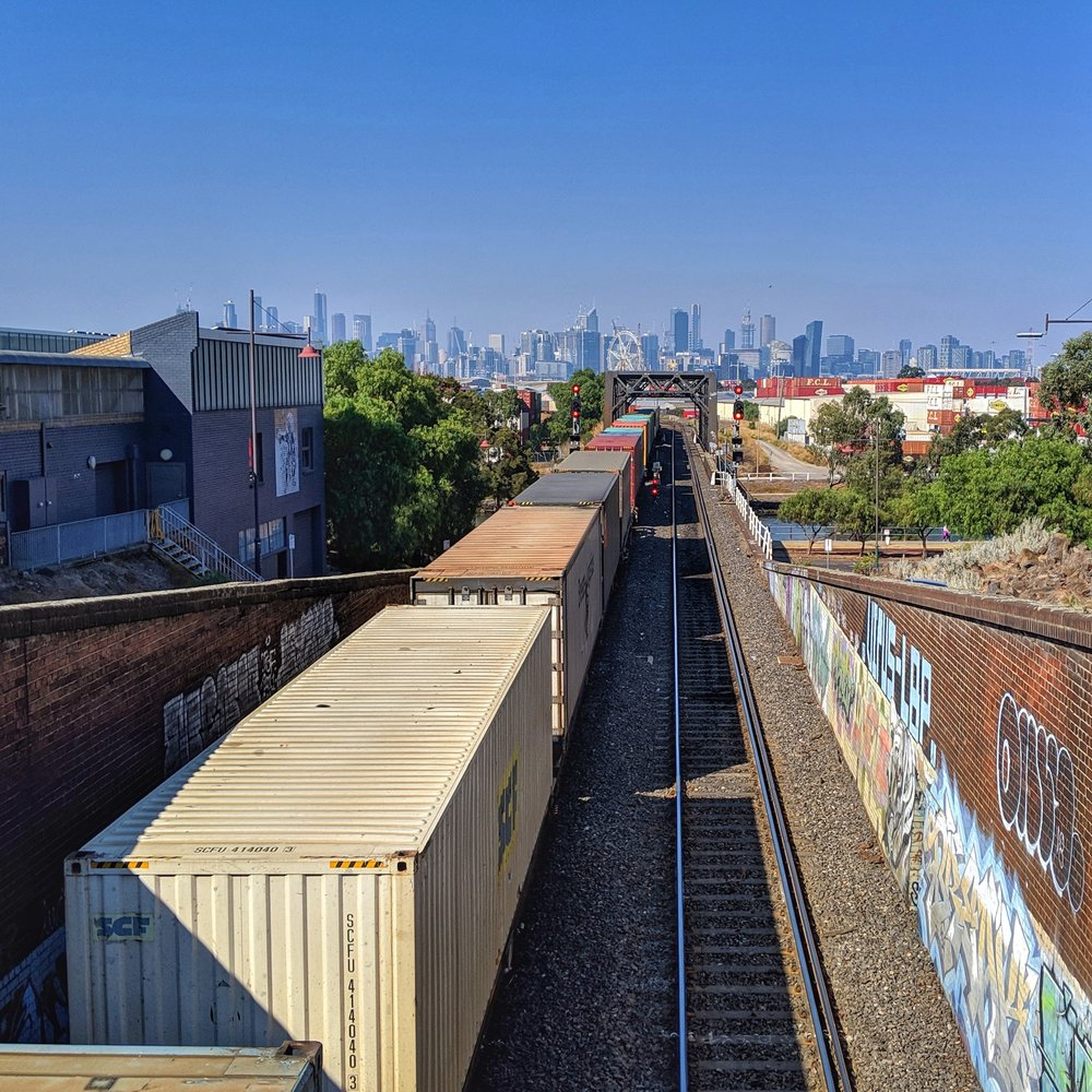 A freight train heading towards Melbourne city on the South Kensington–West Footscray railway line, next to Footscray station.