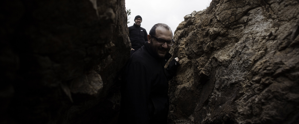 Producer Joshua Cohen explores a cave as Jesse looks on, in the hills of Cerillos, New Mexico