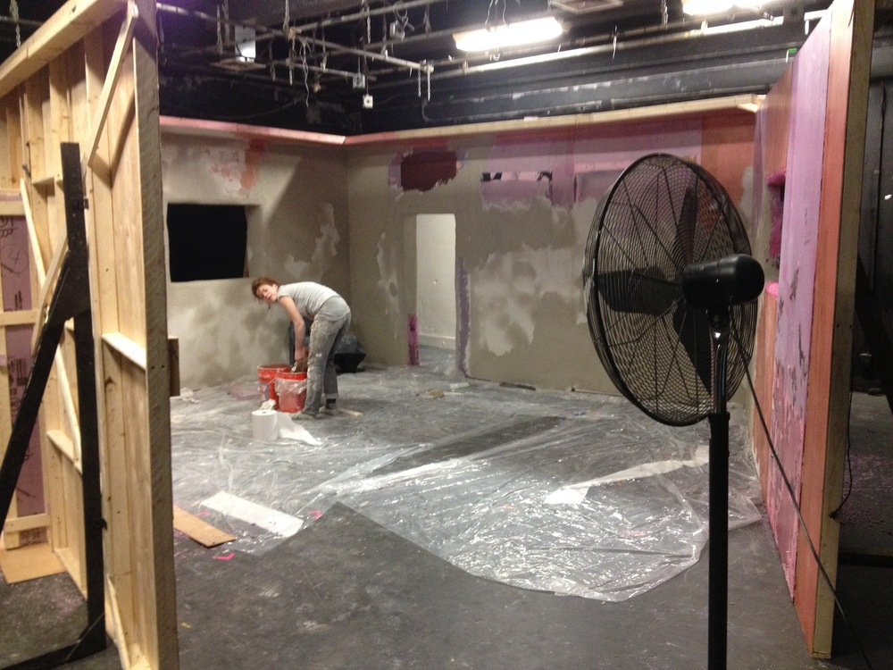 Scenic artists at work applying the wall treatment.