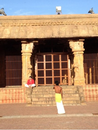 Image of the closed second mandapa attached to the Subrahmanya Shrine. Priest is shown blowing conch before morning services. (Photograph: Hali Mason).