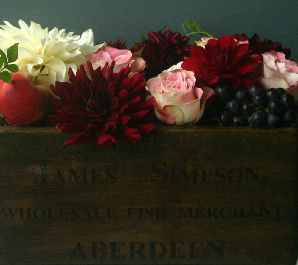 Gorgeous roses, dahlias (and some random fruit) in a vintage fish box