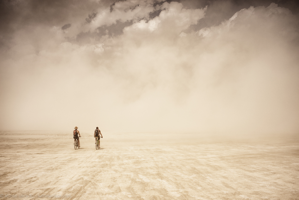 Two cyclists venture out straight into a white out in the middle of the Deep Playa.