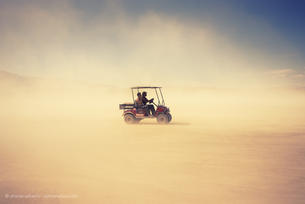 Crew members from Burning Man drive in the desert towards the Man structure.