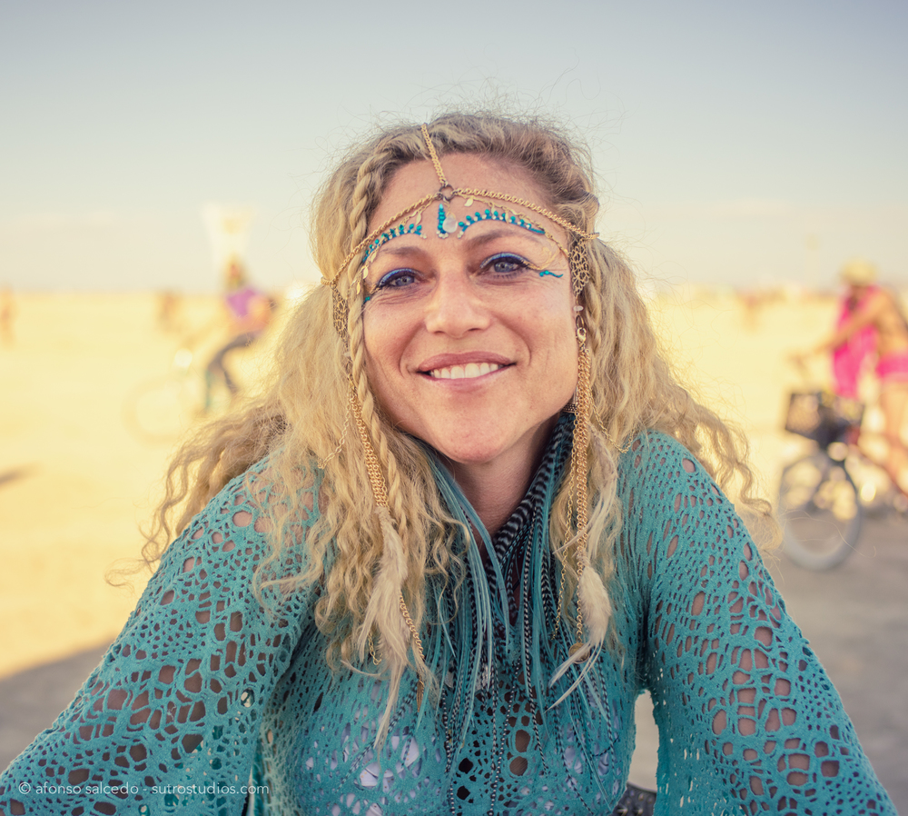 One of the members of day party favorite Pink Mammoth camp, photographed as she bikes across the Playa.