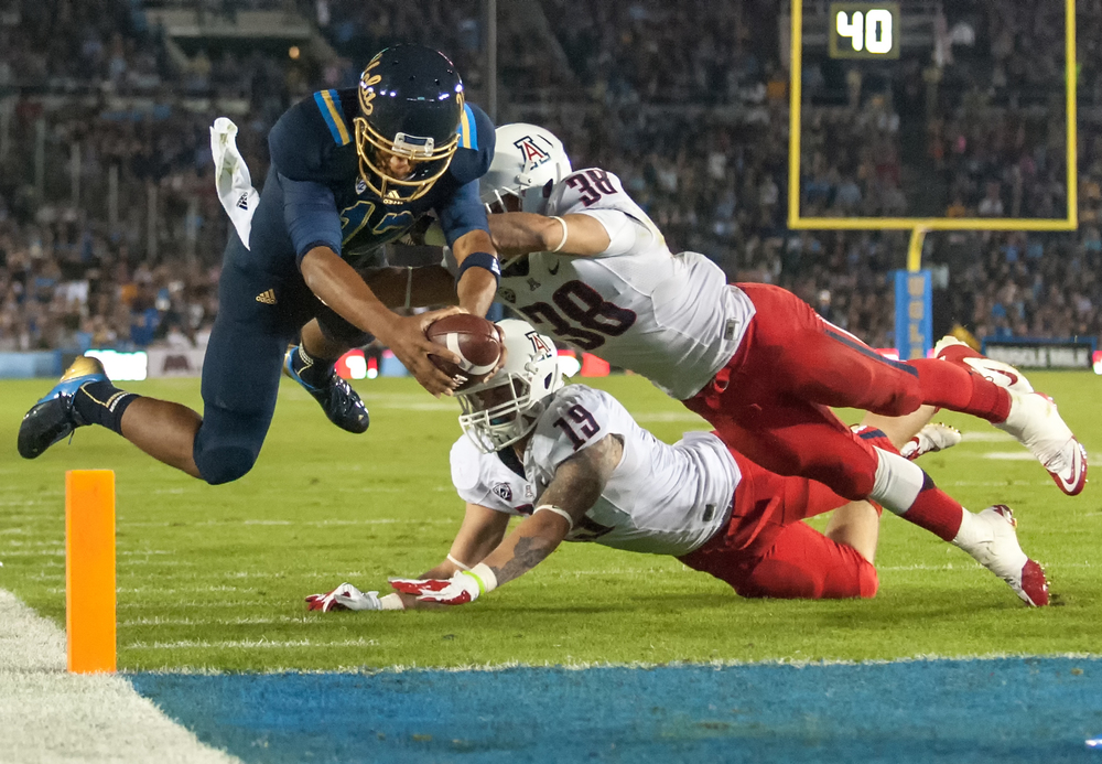 PASADENA, CA – Redshirt freshman quarterback Brett Hundley dives toward the endzone past Arizona sophomore linebacker Hank Hobson (center) and sophomore safety Jared Tevis at the Rose Bowl on Saturday, November 3, 2012.