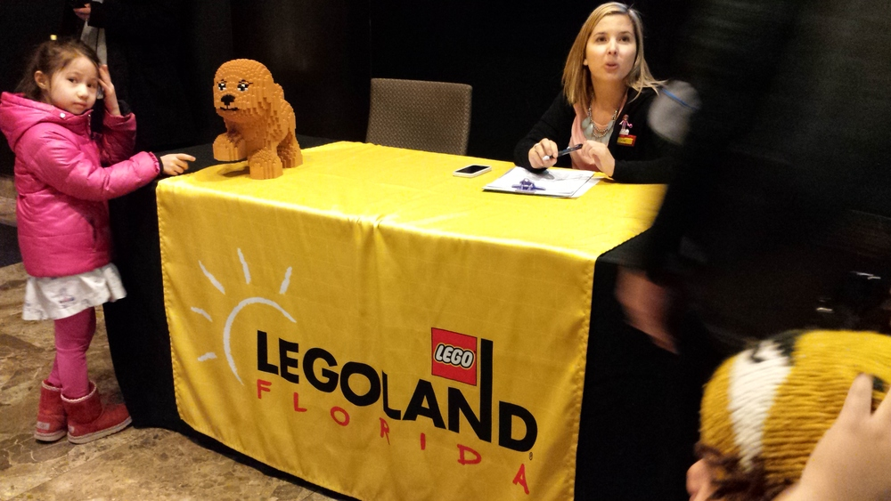 one of the first visitors checks out scarlett the dog at the legoland florida resorts check-in table.