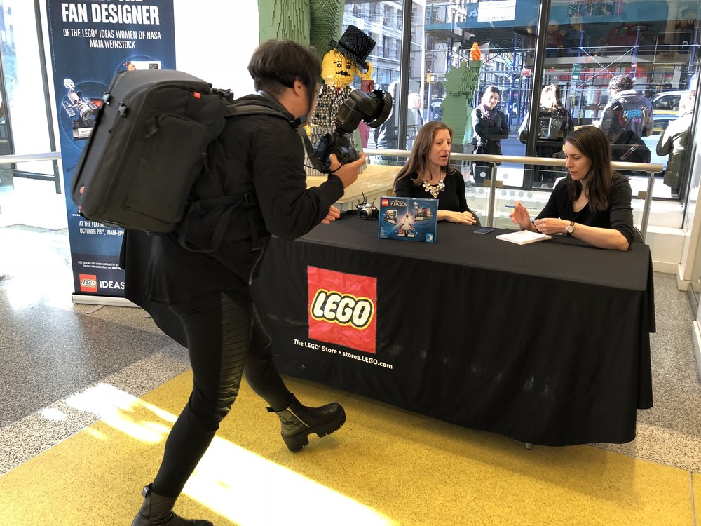 the designer, being interviewed for a feature in scholastic magazine as the line outside the lego store patiently waits