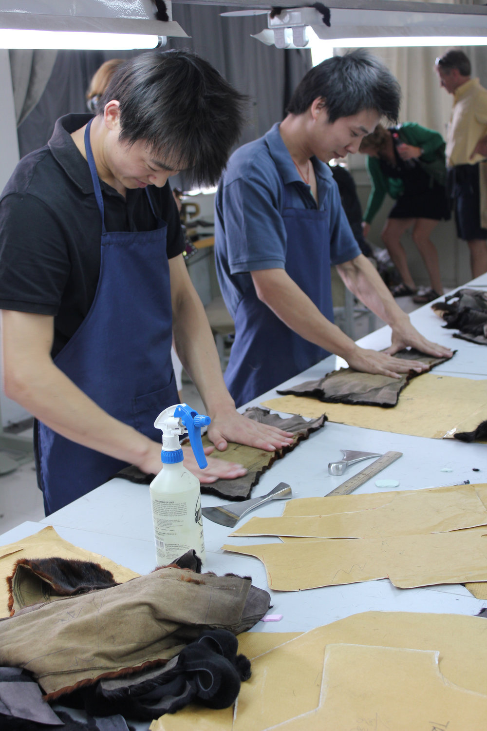 Up in the main manufacturing warehouse, workers match cut pieces of pelts to larger garment patterns.
