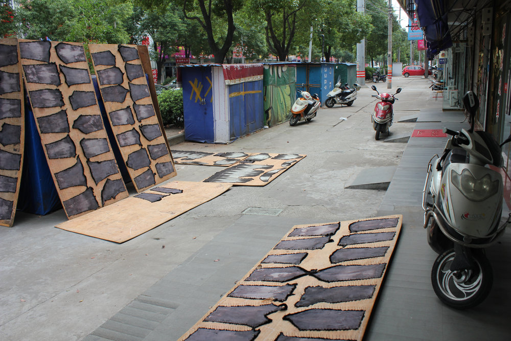 Any available surface is a good enough surface for the neighborhood's workers to lay out patterned goods in process.