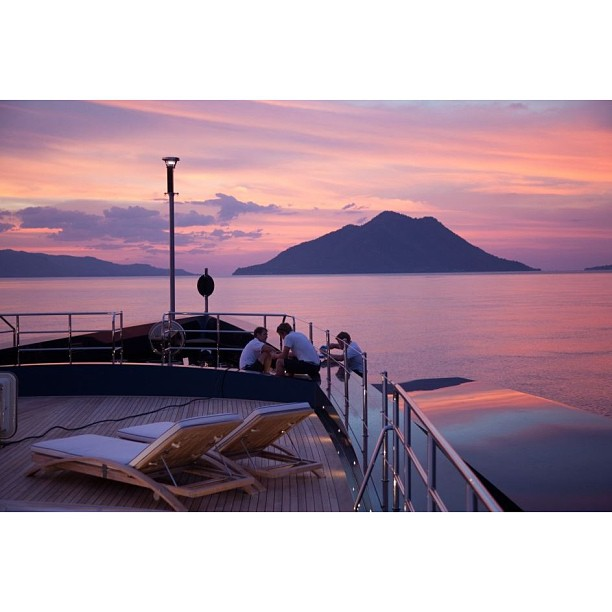 The yachtie lifestyle at its very best. Friends, Sunsets, and Superyachts. Also notice the starboard hull garage for a tender. (Always a clever design strategy to save the aft deck space for amenities and a larger beach club) Photographed taken by Jonny Poupon #sunset#yacht#design#work#yachtie#superyacht#megayacht#lifestyle#freedom#friendship#luxury#beauty#travel