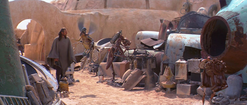 EXT. TATOOINE - MOS ESPA - WATTO'S JUNK YARD - BEHIND SHOP - DAY