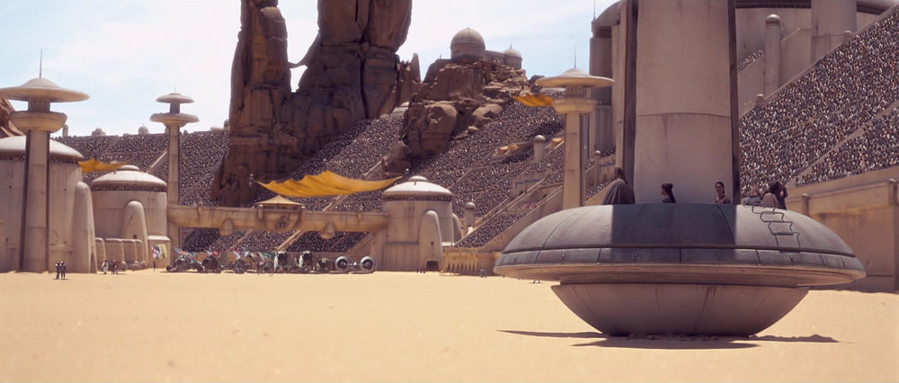 EXT. TATOOINE - MOS ESPA - POD RACE ARENA - DAY