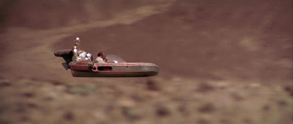 EXT. TATOOINE - WASTELAND - LUKE'S SPEEDER - DAY