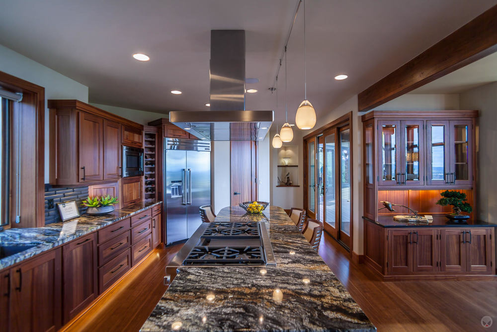 Grantit countertops. Also note: pendant light fixtures, Shaker-style cabinets, stainless steel appliances, and subway tile backsplash.