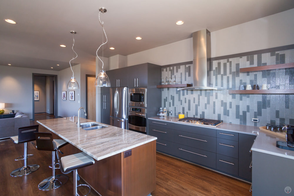 Tiled backsplash. Also note: pendant light fixtures &. stainless steel appliances.