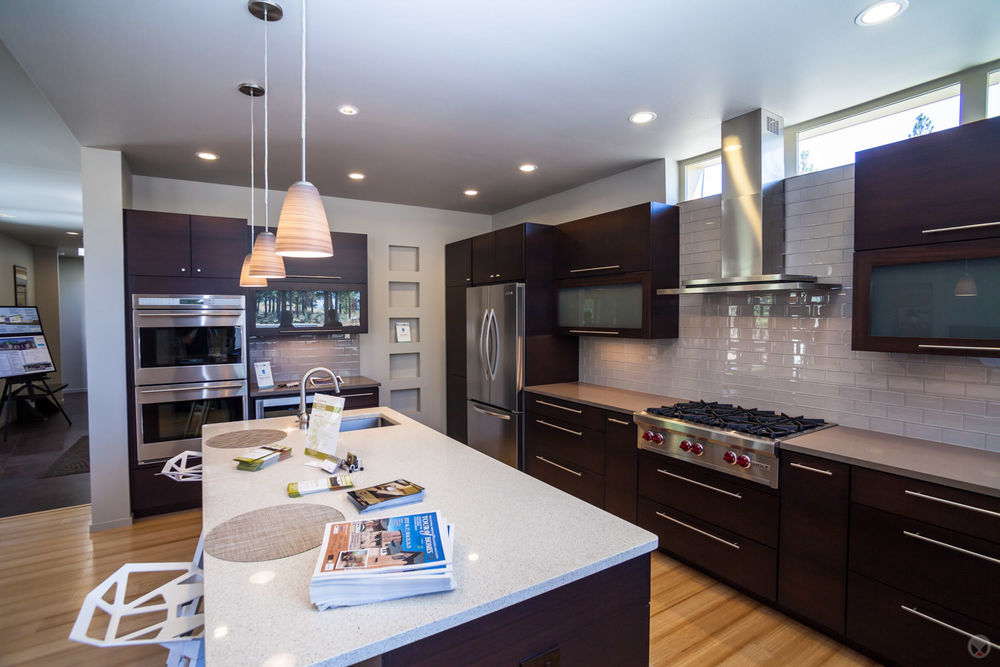 A backsplash of subway tiles. Also note: pendant light fixtures and stainless steel appliances.