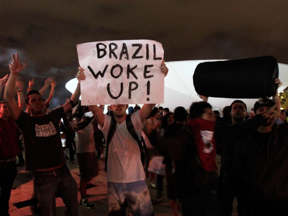 "Brazilian protesters marching through the streets. Great use of the past simple of ""to wake up""!"