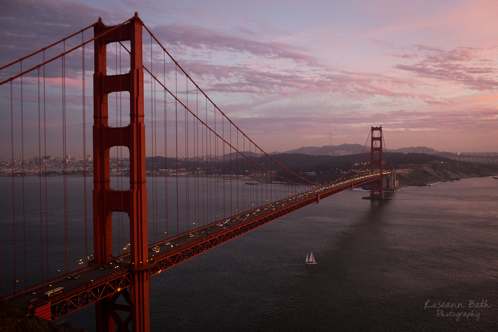 sailboat under golden gate bridge at dusk