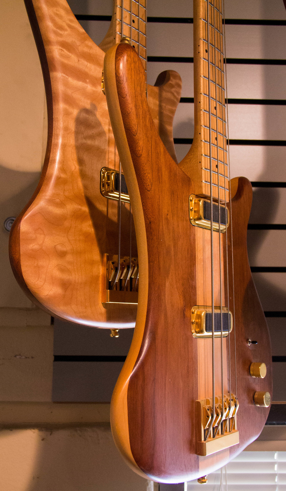 These model 4004 basses are crafted from maple and walnut, sandwiched together. The instrument in the foreground is mostly Walnut; the one in the background features a beautiful curly-maple top.