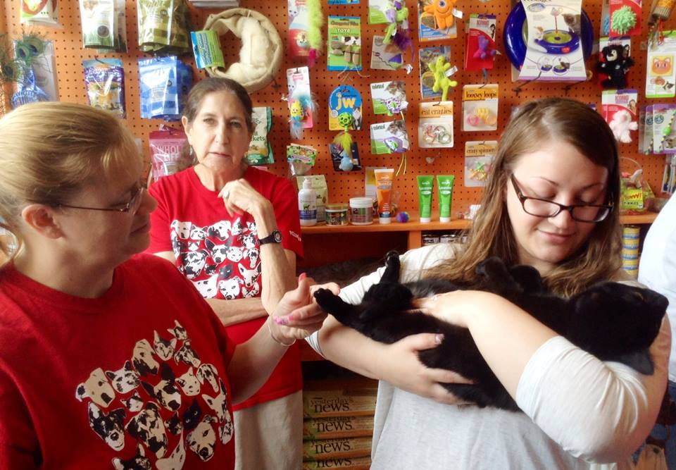 Pauline (center) helps to find a home for a kitty at an adoption event.