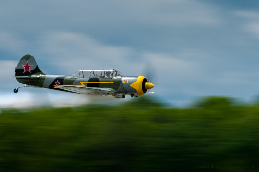 "Yak-52 Flyby. Pilot: Charlie ""V+12"" VandenBossche.  Camera settings:400mm, 1/50 sec, f/29"