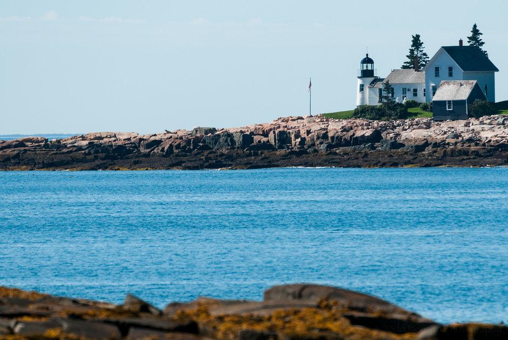 Winter Harbor Light, on Mark Island, Maine, seen from rocky coast of the Schoodic Peninsula portion of Acadia National Park