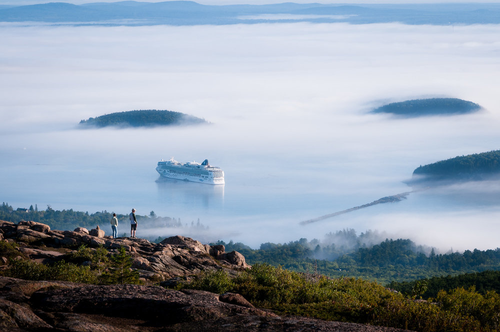 Couple on Cadillac Mountain facing cruise ship in foggy Gulf of Maine