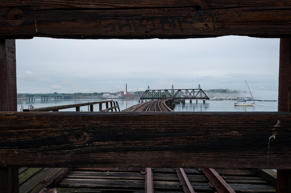 Looking through planks at old railroad bridge with Burnham & Morrill Company factory on distant shore