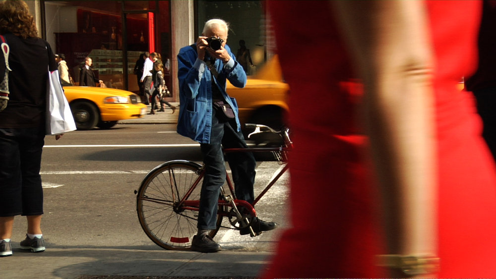 Bill Cunningham photographing in the street, in BILL CUNNINGHAM NEW YORK. A film by Richard Press. A Zeitgeist Films release. Photo credit: First Thought Films / Zeitgeist Films