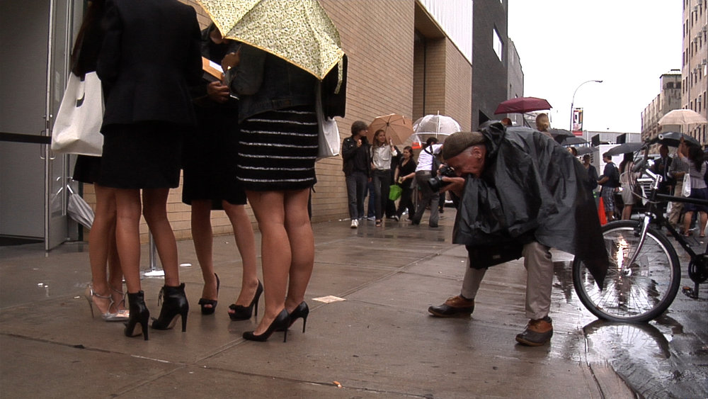 Bill Cunningham photographing in the street, in BILL CUNNINGHAM NEW YORK. A film by Richard Press. A Zeitgeist Films release. Photo credit: First Thought Films / Zeitgeist Films