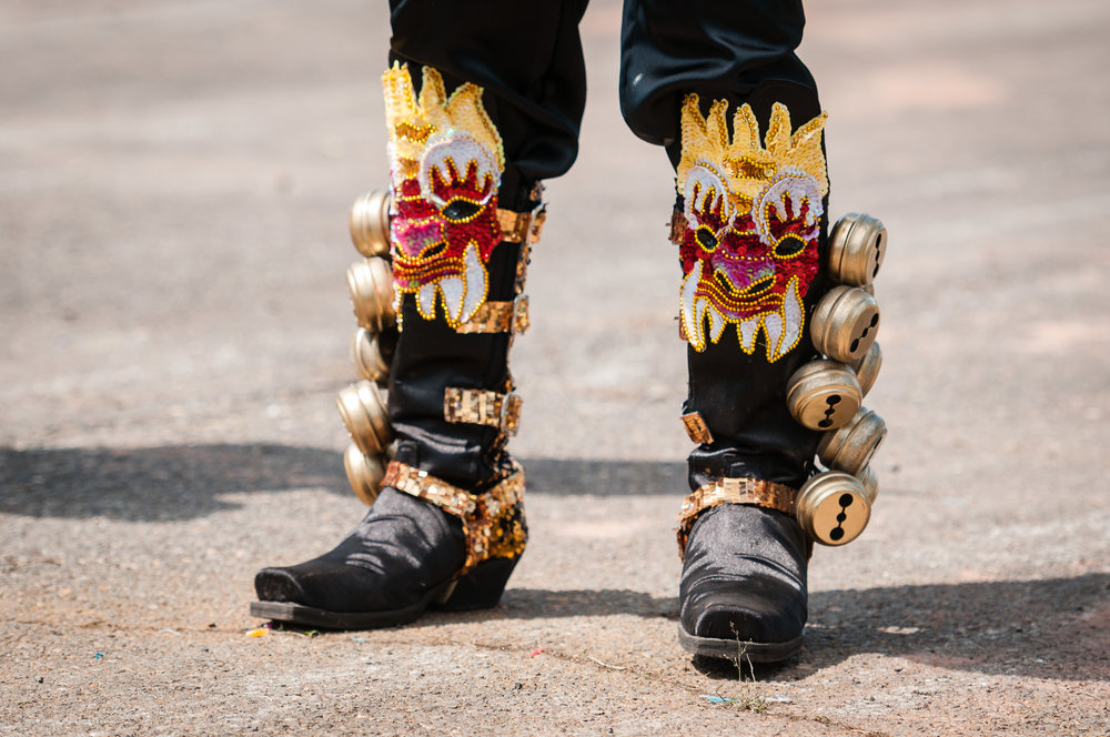 Details of the boots of a member of Fraternidad Folklorica Cultural Caporales Universitarios San Simon Filial VA during their performance of a Caporales dance.