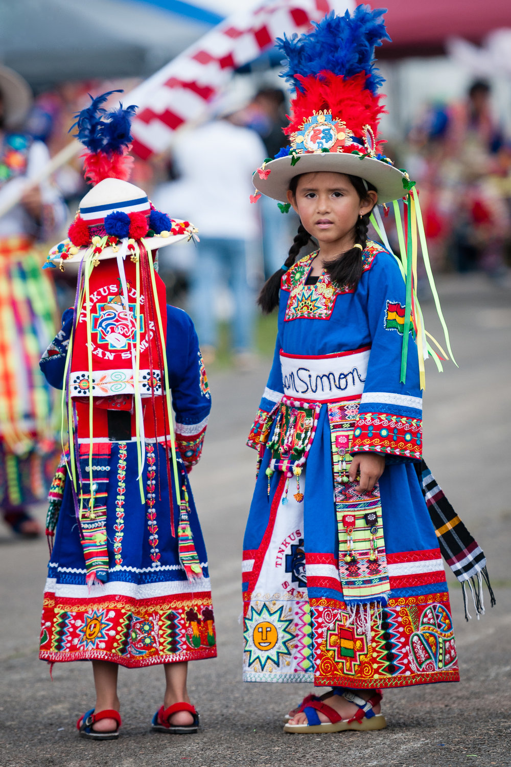 I love this photograph of two young performers with Tinkus de San Simon USA, who performed a Tinkus dance. One performer is looking down the route they would take towards me, and the other is looking back towards the rest of their group.